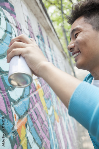 Smiling young man holding a spray can and spray painting on a wall outside