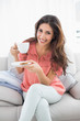 Smiling brunette sitting on her sofa holding cup and saucer