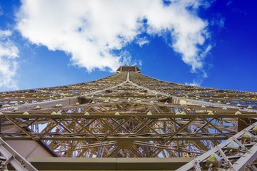 Eiffel tower under clouds and blue sky