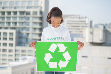 Cute volunteer woman holding recycling sign