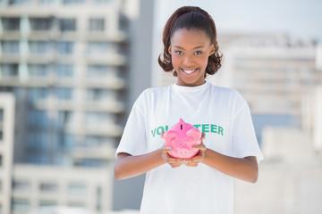 Happy volunteer holding piggy bank