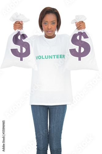 Serious volunteer woman holding money bags