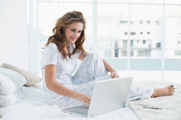Young woman sitting on cosy bed