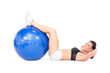 Smiling fit woman developing her abs using exercise ball