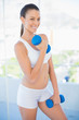 Happy woman lifting dumbbell