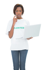 Serious volunteer woman using laptop