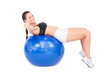 Sporty woman working out with exercise ball giving thumb up to c