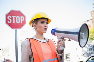 Frowning businesswoman wearing builders clothes holding megaphon
