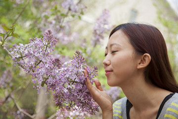 Young woman with eyes closed smelling a flower blossom in the park in springtime