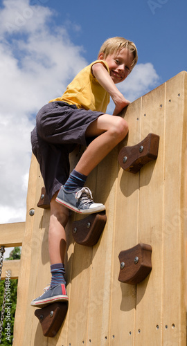 Boy on playground climbing wall