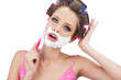 Model in hair curlers shaving her face