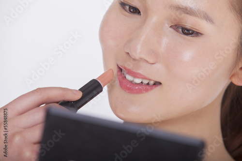 Close up of young woman applying lipstick in a mirror, studio shot