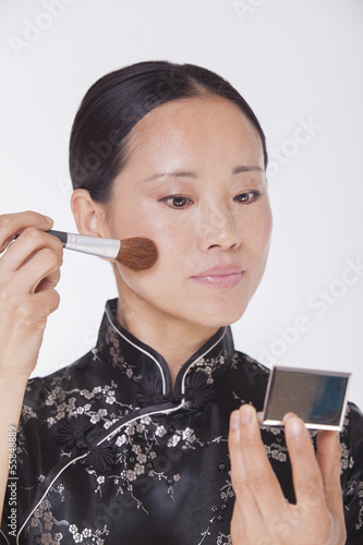 Woman in traditional clothing looking into a mirror and applying make up with a make up brush, studio shot