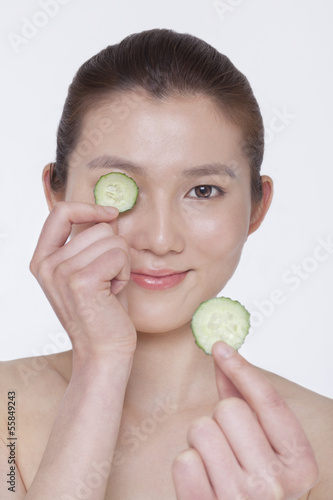 Smiling young woman holding up cucumber slices to put over her eyes, studio shot