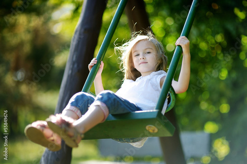 Adorable girl having fun on a swing