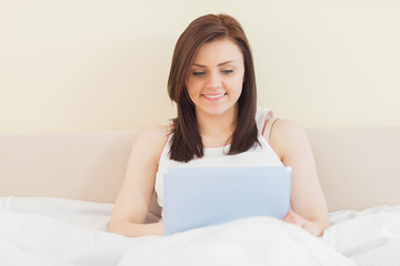Smiling girl using a tablet pc lying on a bed