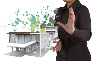 businesswoman hand shows house model and splash colors