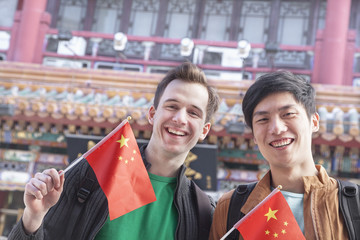 Two young men holding Chinese flags.
