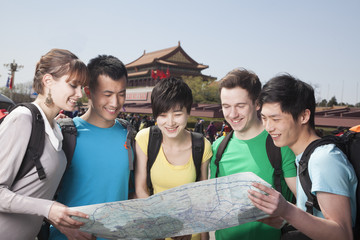 Five people looking at map with Tiananmen Square in background.