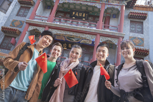 Group of young people holding Chinese flags, portrait.