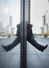 Businessman stepping out into the street, reflection in the glass of the building