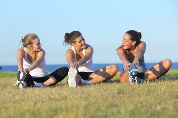 Group of three women stretching after sport