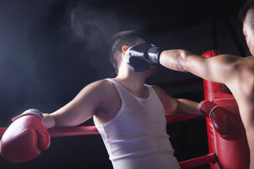 Over the shoulder view of male boxer throwing a knockout punch in the boxing ring