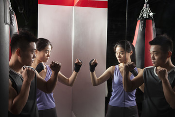 Boxing Instructor and female student practicing stance in front of the mirror at the boxing gym