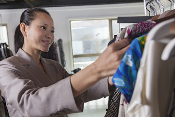 Woman going through clothes at fashion store