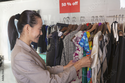 Woman going through clearance clothes at fashion store