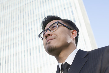 Portrait of young businessman by the world trade center in Beijing, China