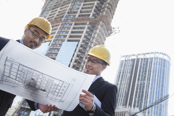 Architects looking at blueprint on construction site, Beijing