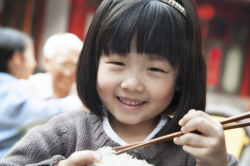 Portrait of little girl eating rice