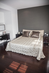 Bright, modern bedroom with beige bedspread.