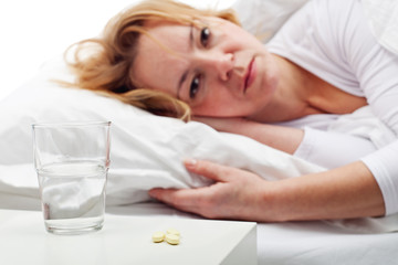 Taking pills - woman laying in bed