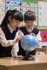Schoolgirls looking at a globe in the classroom