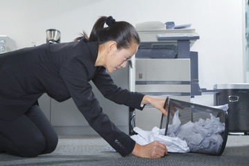 Businesswoman Looking for Papers in Trashcan