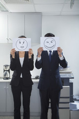Businesspeople Holding Happy Faces on Paper