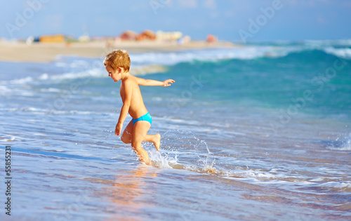 cute kid boy having fun in sea surf
