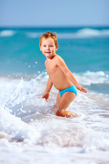 cute kid boy having fun in sea surf, crimea