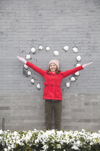 Young woman standing on wall with heart shaped snow balls
