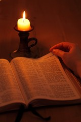 Bible and candle in dark