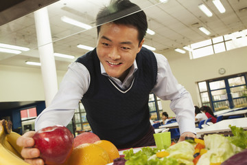 Teacher reaching for healthy food in school cafeteria