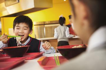 School boy eats noodles in school cafeteria