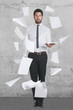 Young businessman standing with flying papers.