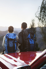 Young couple standing next to the car and looking at the mountains