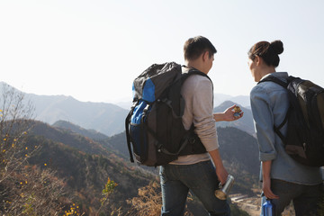 Young couple hiking and looking at the compass