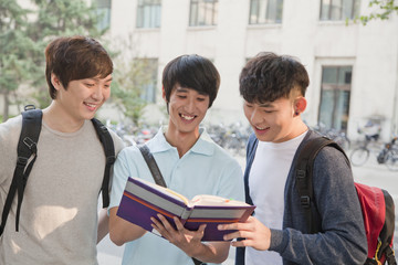 Three students discussing and looking at the book