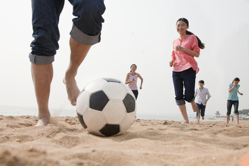 Young Friends Playing Soccer on the Beach
