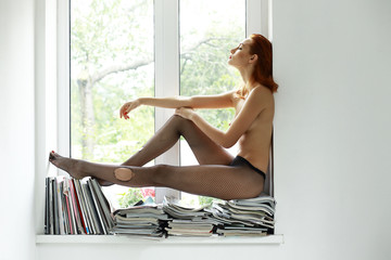 Nude Beauty. Naked Woman in Stockings sitting in Window Sill